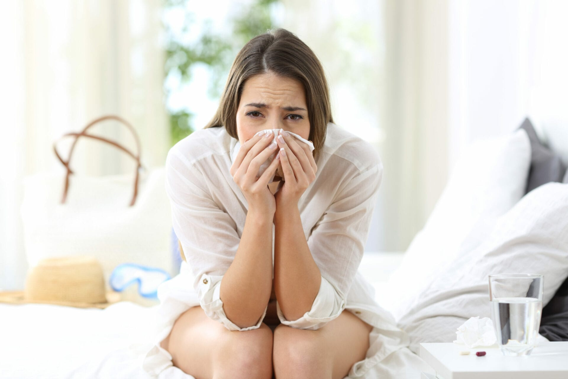 Front view portrait of an ill allergic woman looking at camera sitting on the bed of an hotel room on summer vacations